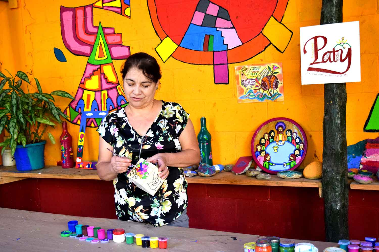 Estelita Perlera showing how to color a La Palma craft to a group of visitors