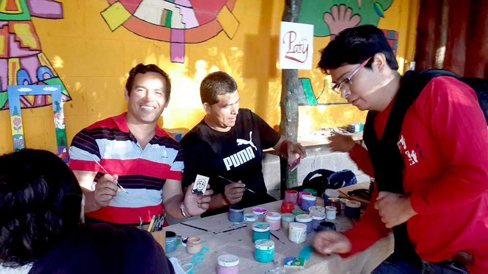 group of young salesians show us their design in the craft painting class