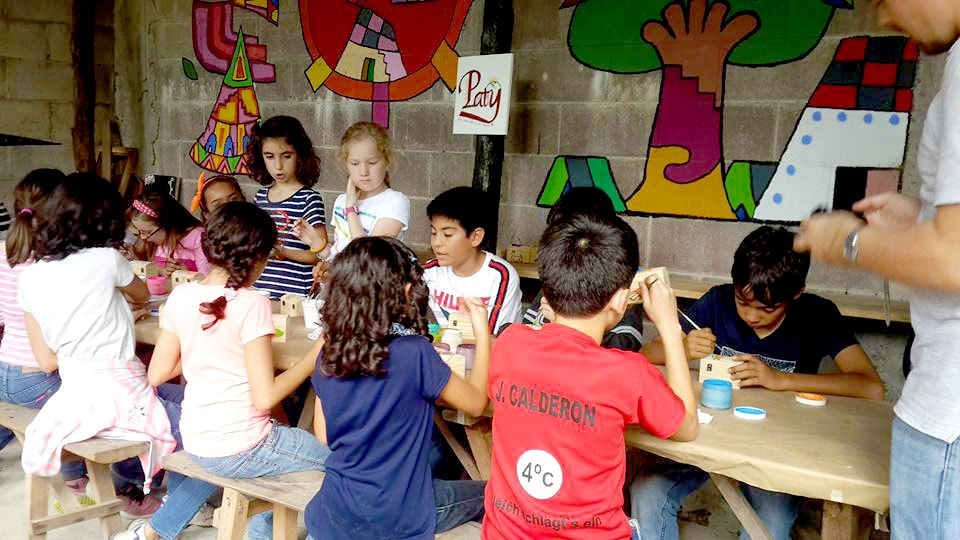 Group of children enjoy themselves and learn to paint their own La Palma craft